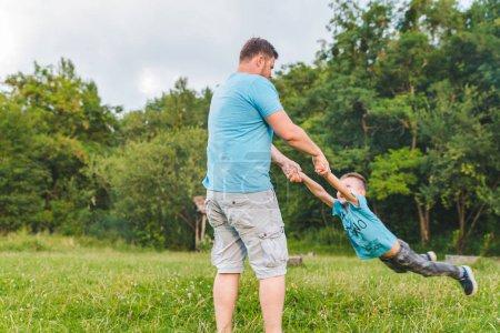 Photo pour Hommes les garçons de filature à champ vert. jouer autour. amusement temps - image libre de droit