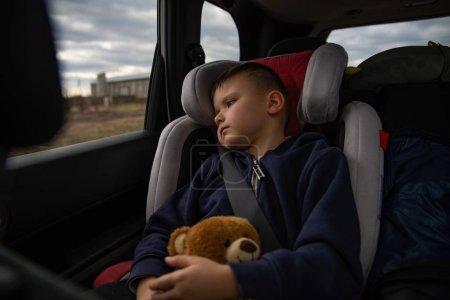 Photo pour Mignon petit garçon avec l'ours pelucheux dans la chaise de voiture aux sièges arrière dans le voyage de route. concept de voyage - image libre de droit