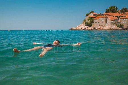 Photo pour Jeune femme jolie, nager dans la mer bleue. plage de Sveti stefan. heure d'été - image libre de droit