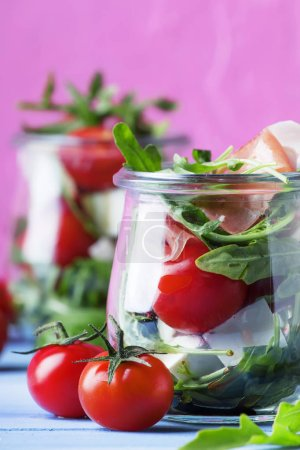 Summer salad with arugula, soft cheese, cherry tomatoes and prosciutto in glass jars, festive background, selective focus
