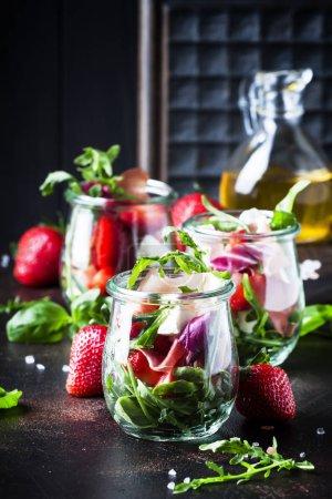 Ensalada de verano con rúcula, queso blando, rojo fresa y prosciutto en vidrio jarras de mesa negro, enfoque selectivo