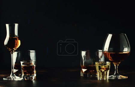 Set of strong alcoholic drinks in glasses and shot glass in assortent: vodka, rum, cognac, tequila, brandy and whiskey