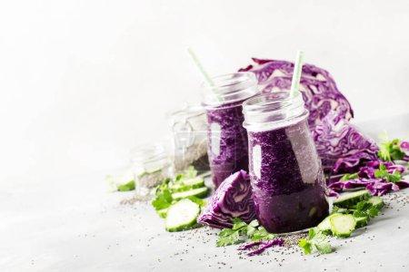 Photo pour Smoothies détox purple vegan sain ou jus de chou rouge, concombre avec graines de clerbois dans des bouteilles en verre sur fond gris - image libre de droit