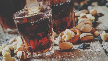 Cola glasses, sweet and savory snacks, old wooden table, unhealthy food