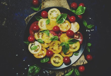 Salad from colorful tomatoes, green basil, low key,