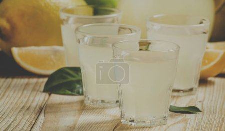 Homemade lemon liqueur and fresh lemons and limes on a wooden background