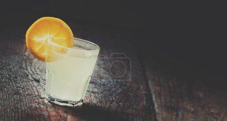 Single glass of vodka with lemon and lemon slice on an old dark wood background