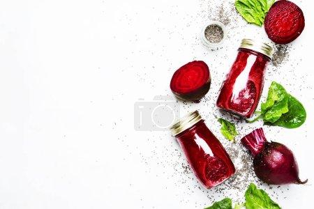 Photo pour Délicieux smoothies à la betterave dans des bouteilles en verre avec chia sur fond alimentaire blanc, vue de dessus - image libre de droit