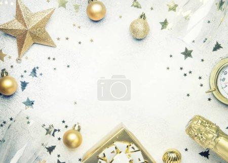 Composition de Noël ou du nouvel an, le cadre, fond gris avec des décorations de Noël or, étoiles, flocons de neige, boules, réveil, boîte de cadeau et bouteille de champagne, haut de la page vue