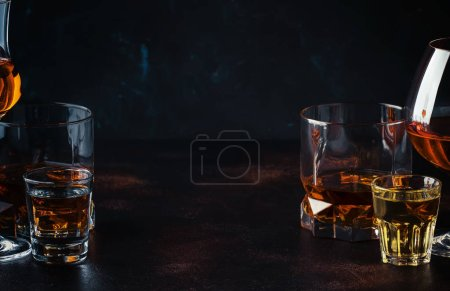 Photo for Selection of strong alcoholic drinks in glasses and shot glass in assortent: vodka, rum, cognac, tequila, brandy and whiskey. Dark vintage background, selective focus - Royalty Free Image