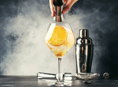 Photo for Preparation of Aperol spritz cocktail, barman pours bitter from jigger, summer Italian low-alcohol cold drink, black bar counter background, summer mood concept. Selective focus - Royalty Free Image