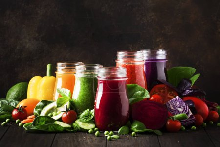 Photo pour Jus et smoothies végétaliens multicolores à base de tomates, carottes, poivrons, choux, épinards, betteraves en bouteilles de verre sur table de cuisine rustique, concept végétarien d'aliments et de boissons, mise au point sélective - image libre de droit