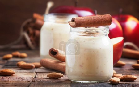 Photo for Healthy eating for weight loss: smoothie from red apples, banana, almonds and cinnamon, selective focus - Royalty Free Image