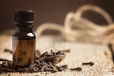Photo pour Huile essentielle de clou de girofle, bouteille brune, fond en bois ancien, mise au point sélective - image libre de droit