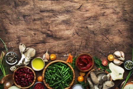 Photo for Food cooking background, ingredients for preparation vegan dishes, green bean, vegetables, roots, spices, mushrooms and herbs. Healthy vegetarian food concept. Rustic wooden table, top view, copy space, border - Royalty Free Image