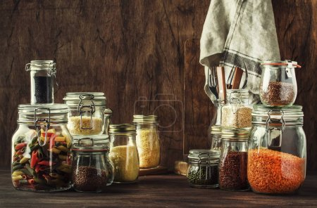 Photo pour Food set. Raw cereals, pasta, groats, organic legumes and useful seeds in glass jars. Vegan source of protein and energy resources. Rustic wooden kitchen table background. - image libre de droit