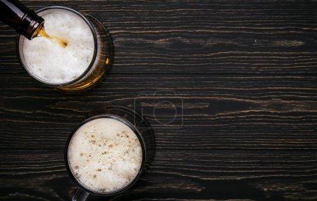Bière foncée, ale ou stout est versé dans le verre, comptoir de bar en bois sombre, espace pour le texte, vue du dessus