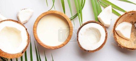 Photo pour Noix de coco et bol de lait de coco sur fond gris. Aliments et boissons sains. Bannière panoramique avec espace de copie - image libre de droit