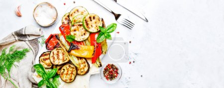 Photo for Grilled colorful vegetables, aubergines, zucchini, pepper with spice and green basil on serving board on white background. Panoramic banner with copy space - Royalty Free Image