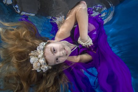 Photo for Girl in long, lilac dresses wearing poses underwater - Royalty Free Image