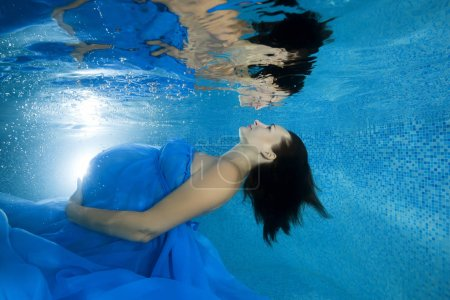 Photo for A pregnant woman in a blue dress looks at her reflection by the underwater in the pool - Royalty Free Image