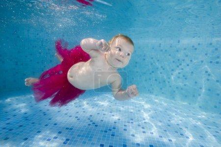 Photo pour Petite fille en jupe nage sans eau dans la piscine - image libre de droit