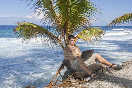 Mann arbeitet am Strand. attraktiver Mann mit Laptop, der in einer Palme am tropischen Strand sitzt. junger Mann am Laptop am tropischen Strand in einer Palme. Arbeit und Urlaub. Symbolbild, digitale Nomaden, Mann sitzt mit Laptop auf T