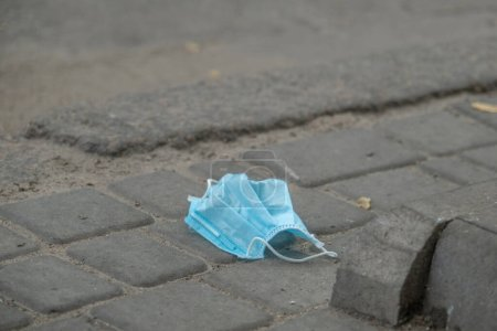 Discarded medical face mask lies on the sidewalk. Face masks polluting streets of the city since Coronavirus COVID-19. Soft focus.