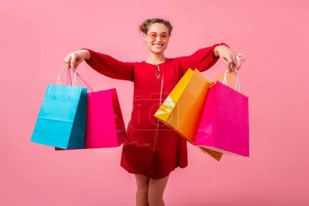 Photo pour Attrayant heureux drôle émotion femme élégante shopaholic en robe rouge tendance tenant des sacs à provisions colorés sur fond de studio rose isolé, vente excitée, tendance de la mode printemps été - image libre de droit