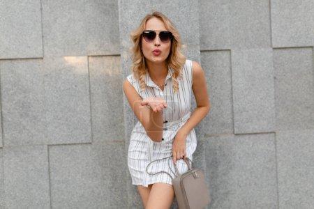 Photo pour Jeune femme élégante attrayante avec une coiffure bouclée blonde marchant dans la rue de la ville en été robe à rayures blanches de style de mode portant des lunettes de soleil tenant sac à main - image libre de droit