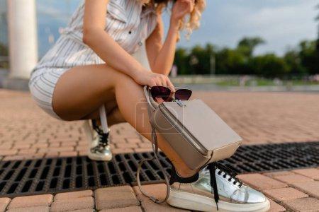 Photo pour Accessoires de femme élégante marchant dans la rue de la ville en robe de style mode d'été portant des lunettes de soleil, baskets, sac à main sac à main gris - image libre de droit