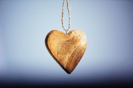 Photo for Closeup view of simple wooden heart on chain - Royalty Free Image