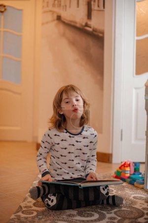 Photo pour Petit garçon avec syndrome du duvet avec livre à la maison - image libre de droit