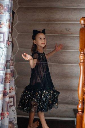 Photo pour Petite fille mignonne en robe noire marchant à la maison - image libre de droit