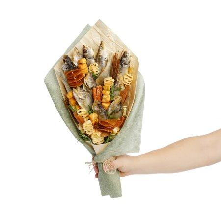Photo pour Bouquet composé de salé stockfish de différentes races, tranches de calmar séché et autres poisson est dans une main masculine sur le fond blanc - image libre de droit