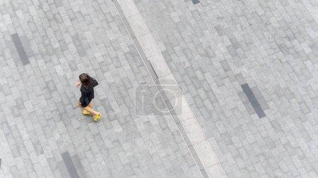 Photo pour Les gens marchent sur le trottoir piéton rue de la ville sur la chaussée en béton avec le groupe de l'homme et de la femme de la mode. (Photo aérienne urbaine de la ville) - image libre de droit