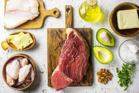 Photo pour Aliments de régime cétogène. Fond de nourriture équilibrée faible en glucides. Poisson, viande, fromage, noix sur un fond blanc. Saine alimentation équilibrée avec teneur élevée en graisses saines. Régime pour le cœur et les vaisseaux sanguins. - image libre de droit