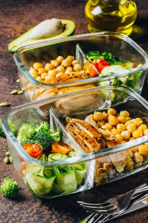 Photo for Healthy meal prep containers with chickpeas, chicken, tomatoes, cucumbers, avocados and broccoli. Top view - Royalty Free Image