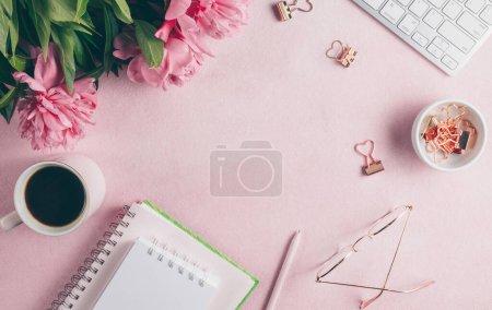 Photo pour Espace de travail bureau féminin avec pivoine rose, clavier, tasse de café, cosmétiques, lunettes, rouge à lèvres, carnet vide sur fond blanc. Couché plat, vue du dessus . - image libre de droit