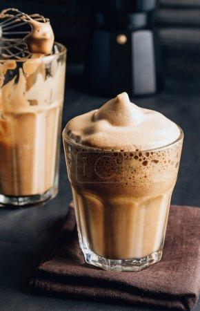 Photo pour Café instantané fouetté. Nouvelle tendance populaire de la nourriture et des boissons. Un verre de café coréen Dalgona avec du lait d'avoine sur fond sombre. Concentration sélective - image libre de droit