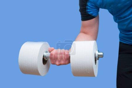 Foto de Concepto de papel higiénico y mancuerna para cuarentena domiciliaria. La mano de un hombre sostiene una mancuerna de papel higiénico sobre fondo azul. de pie en casa. chelter en su lugar. - Imagen libre de derechos