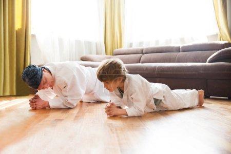 Photo pour Papa et fils en kimono blanc s'entraînent à la maison. quarantaine. concept de santé. Virus Corona. à la maison. Chelter en place. séances d'entraînement à domicile - image libre de droit