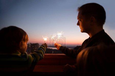 Photo pour Papa de famille et deux enfants avec Sparklers Au coucher du soleil sur le balcon de la maison. Virus Corona. à la maison. Chelter en place. fin d'une quarantaine. vacances à domicile - image libre de droit