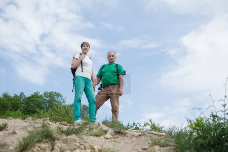 Photo pour Couple âgé avec sacs à dos voyage dans les montagnes. Couple sénior marchant dans la nature - image libre de droit