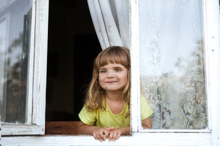 Photo for Happy child girl looks out of the open window of the old village house. - Royalty Free Image