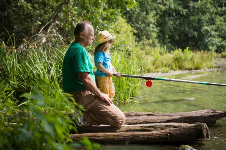 Photo for Senior man fishing with grandson on the lake. - Royalty Free Image