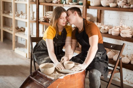 Photo for Couple in casual clothes and aprons making ceramic pot on pottery wheel in workshop - Royalty Free Image