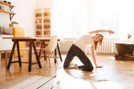 Photo pour Transformer la passion en travail. Femme s'étirant dans la chambre à la maison. Style de vie sain et sportif. Fitness fille sportive faisant yoga exercice de fitness. Rituel du matin. humeur détendue - image libre de droit