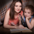 Family Mom and little son reading a book with a fl...