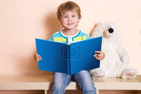 Photo for Cheerful little child boy with book - Royalty Free Image